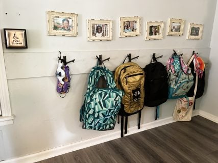 Shannon Dingle's Raleigh, North Carolina, home is outfitted with hooks for each of the six children's backpacks with their photo hanging above the hooks. RNS photo by Yonat Shimron