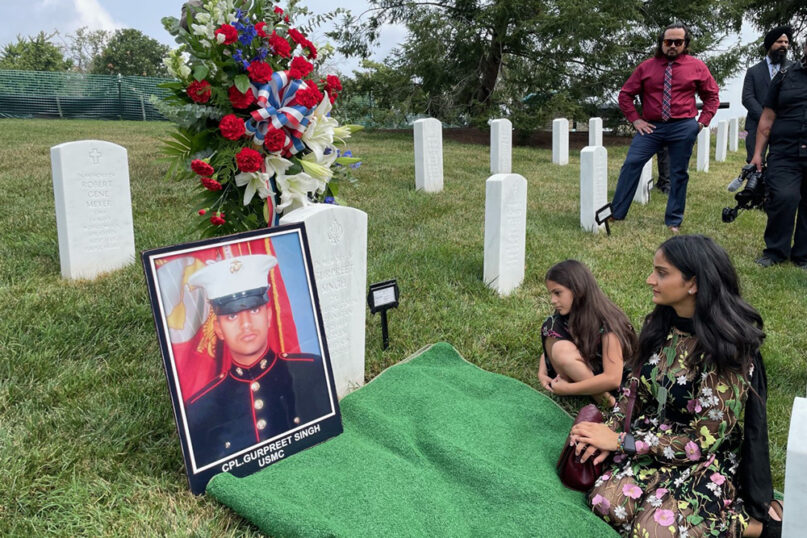 Manpreet Kaur sits on a mat at the grave of her brother, Cpl. Gurpreet Singh, at Arlington National Cemetery, accompanied by Singh's niece. Singh served in the U.S. Marine Corps and was killed in Afghanistan in 2011. He is only the second Sikh soldier to be buried in the cemetery. Photo courtesy of Sikh American Veterans Alliance