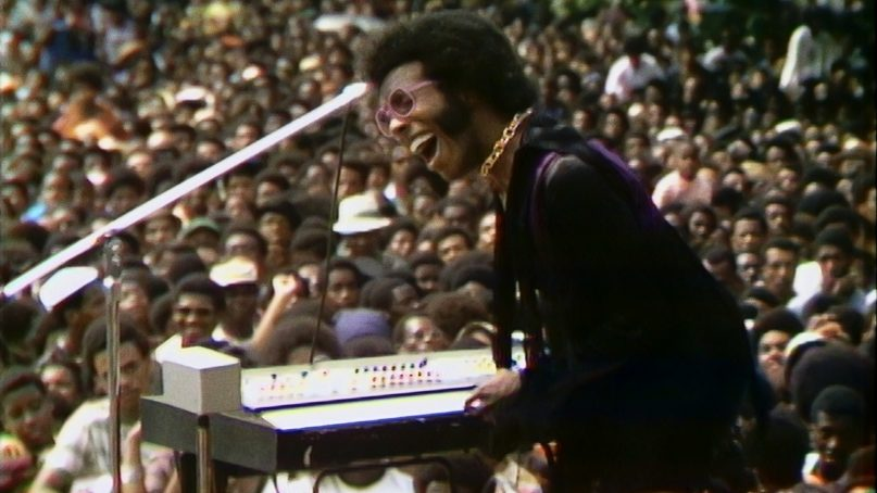 """Sly Stone performs at the Harlem Cultural Festival in 1969, featured in the documentary """"Summer of Soul.""""  Photo courtesy of Searchlight Pictures. © 2021 20th Century Studios. All rights reserved."""