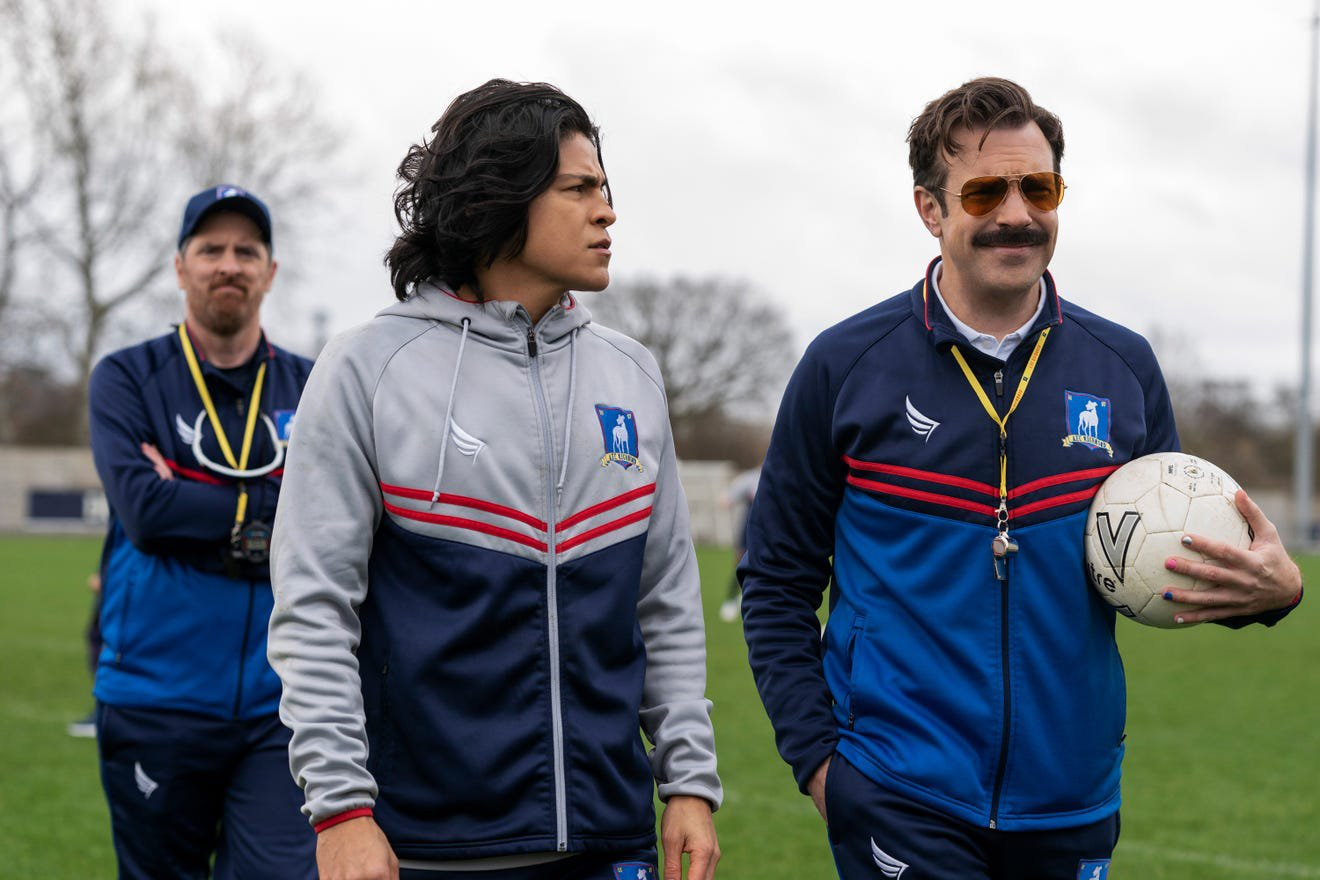 """Brendan Hunt as Coach Beard, from left, Cristo Fernández as star player Danny Rojas, and Jason Sudeikis as Ted Lasso in the Apple TV+ series """"Ted Lasso."""" Photo by Colin Hutton/Apple TV+"""