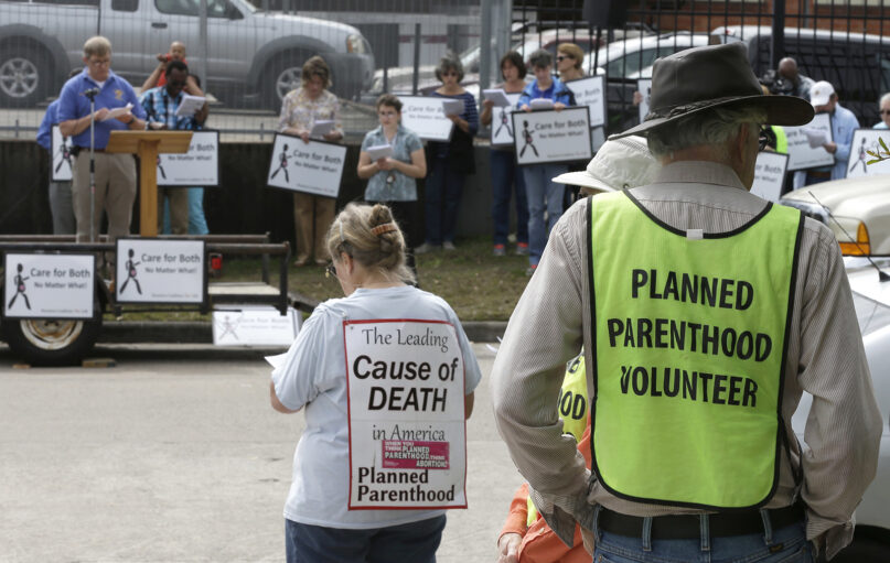 Planned Parenthood volunteers, right,  keep watch over protesters outside a Planned Parenthood, Wednesday, March 2, 2016, in Houston. (AP Photo/Pat Sullivan)