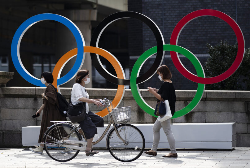 People walk by the Olympic rings installed by the Nippon Bashi bridge in Tokyo on Thursday, July 15, 2021. (AP Photo/Hiro Komae)