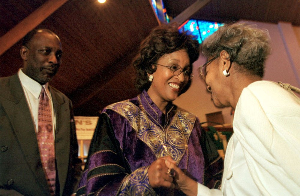 Bishop Vashti Murphy McKenzie, center, outgoing pastor of Payne Memorial African Methodist Episcopal Church in Baltimore, bids longtime member Helen Thorton farewell on her last Sunday at the church in Sept. 2000. At left is her husband, Stan McKenzie. Photo by Carl Bower