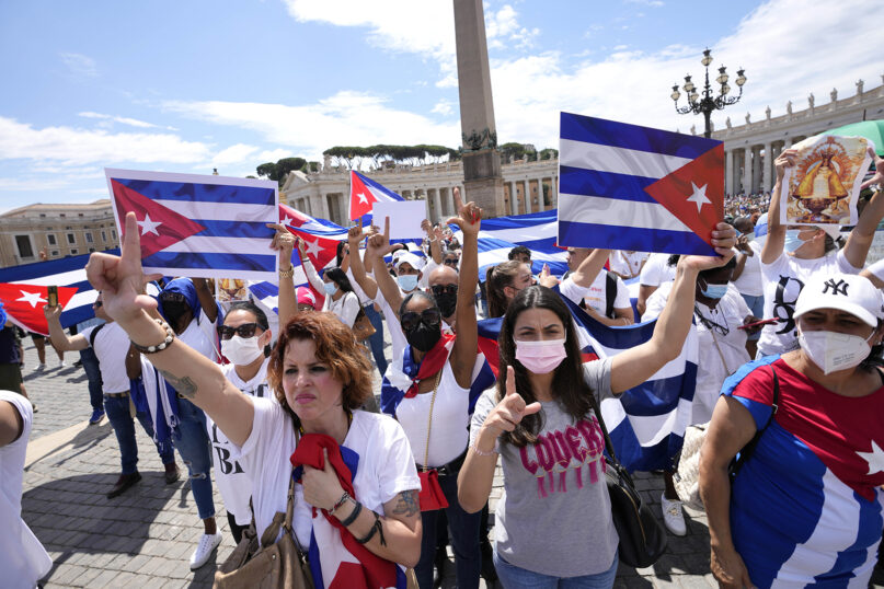 """Members of Italy's Cuban community display Cuban flags in St. Peter's Square during Pope Francis' Angelus noon prayer at the Vatican, July 18, 2021. The pope cited unrest in Cuba, expressing a prayer so that Cubans have a """"more just and fraternal society."""" (AP Photo/Alessandra Tarantino)"""
