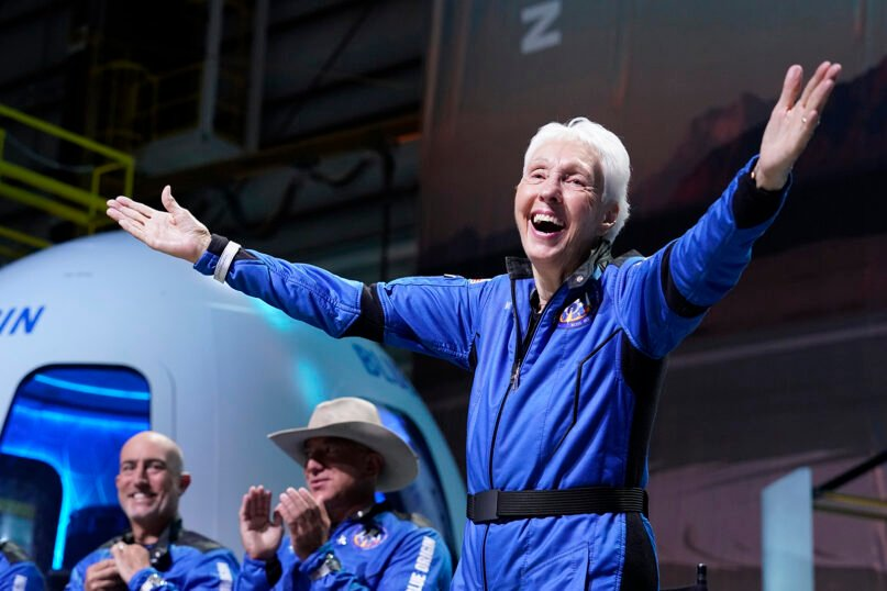 Wally Funk, right, describes their flight experience as Mark Bezos, left, and Jeff Bezos, left, center, founder of Amazon and space tourism company Blue Origin, applaud from the spaceport near Van Horn, Texas, Tuesday, July 20, 2021. (AP Photo/Tony Gutierrez)