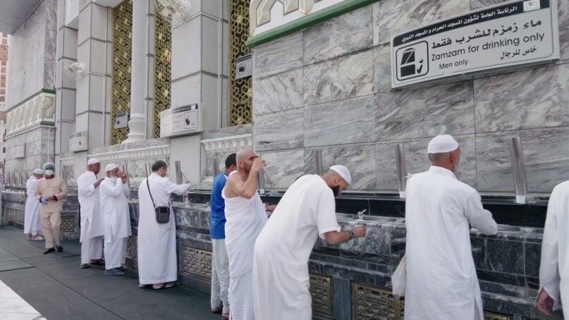 Pilgrims drink water from a Zamzam water fountain during a pre-COVID hajj in Mecca, Saudi Arabia. Video screen grab
