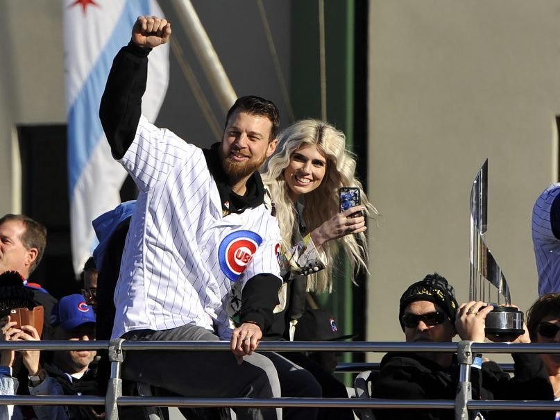 Chicago Cubs baseball player Ben Zobrist pumps his fist while his wife, Julianna, looks on outside Wrigley Field during a parade honoring the World Series champions Nov. 4, 2016, in Chicago. The couple is divorcing. (AP Photo/Paul Beaty)