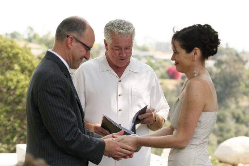 Huell Howser serves as a wedding officiant during a backyard wedding. For many non-religious couples, choosing a friend or family member to officate their wedding is preferred to a spiritual leader. Photo by Nathan Gibbs/Flickr