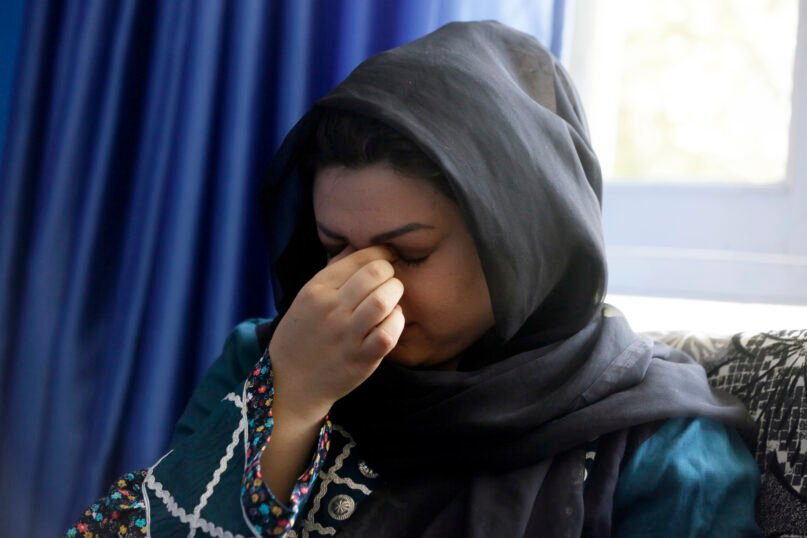 """Zarmina Kakar, a women's rights activist, cries during an interview with The Associated Press in Kabul, Afghanistan, Aug. 13, 2021. Kakar was a year old when the Taliban entered Kabul the first time in 1996, and she recalled a time when her mother took her out to buy her ice cream, back when the Taliban ruled. Her mother was whipped by a Taliban fighter for revealing her face for a couple of minutes.   """"Today again, I feel that if Taliban come to power, we will return back to the same dark days,"""" she said. (AP Photo/Mariam Zuhaib)"""