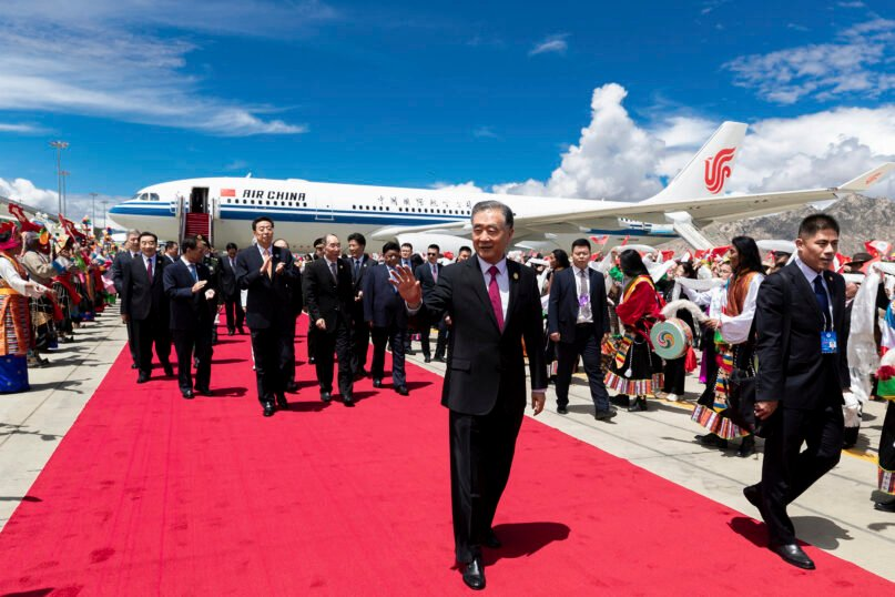 In this photo released by Xinhua News Agency, Wang Yang, chairman of the Chinese People's Political Consultative Conference, center, waves as he arrives in Lhasa to attend the ceremony to commemorate the 70th anniversary of Tibet liberation, in Lhasa in western China's Tibet Autonomous Region on Aug. 18, 2021. (Huang Jingwen/Xinhua via AP)