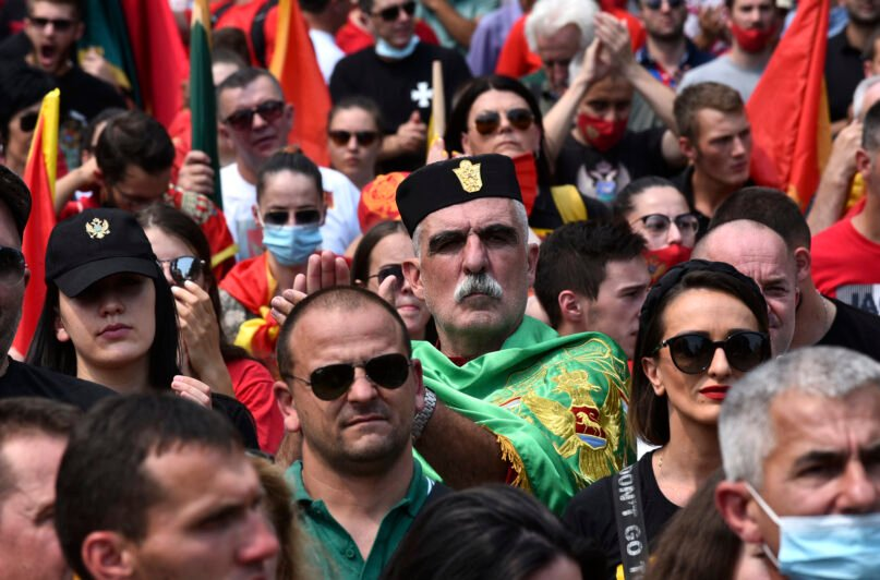 A protester, wearing a traditional hat applauds during a rally in Montenegro's former capital, Cetinje, Sunday, Aug. 22, 2021. Several thousand people demonstrated on Sunday in Montenegro over the planned inauguration of the new head of the Serbian Orthodox Church in the small Balkan state. (AP Photo/Risto Bozovic)