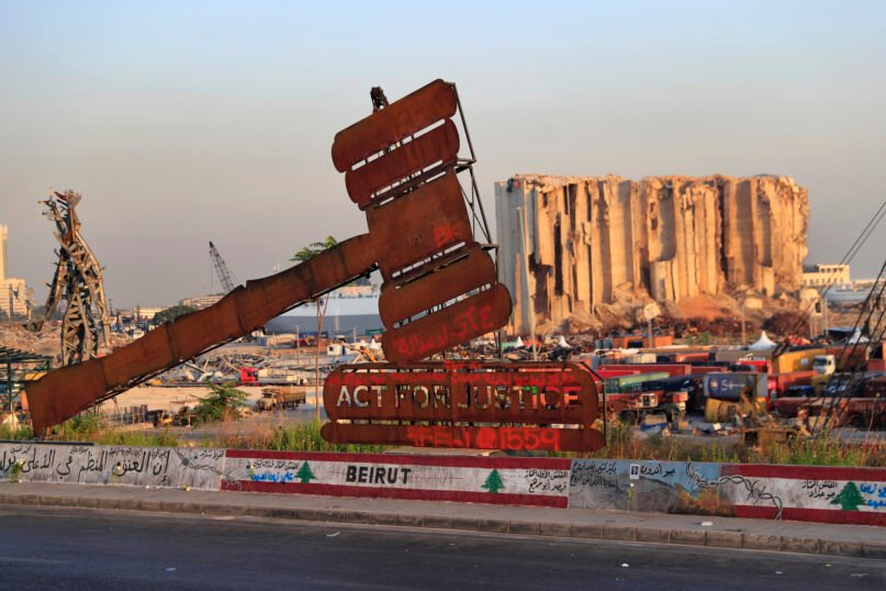 A justice symbol monument is seen in front of towering grain silos that were gutted in the massive August 2020 explosion at the port that claimed the lives of more than 200 people, in Beirut, Lebanon, Wednesday, Aug. 4, 2021. A year after the deadly blast, families of the victims are consumed with winning justice for their loved ones and punishing Lebanon's political elite, blamed for causing the disaster through their corruption and neglect. (AP Photo/Hussein Malla)