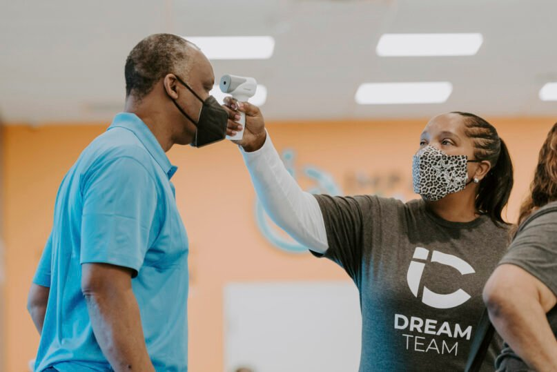 In this photo provided by Impact Church, a man gets his temperature taken during a vaccination event held by Impact Church on Aug. 8, 2021, in Jacksonville, Fla. The church has lost seven members in the last few weeks, according to Pastor George Davis. (Impact Church via AP)