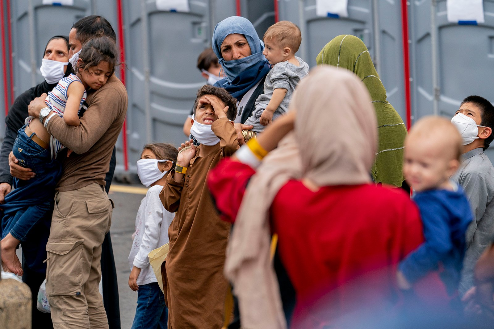 People evacuated from Afghanistan step off a bus as they arrive at a processing center in Chantilly, Virginia, on Aug. 23, 2021, after arriving on a flight at Dulles International Airport. (AP Photo/Andrew Harnik)
