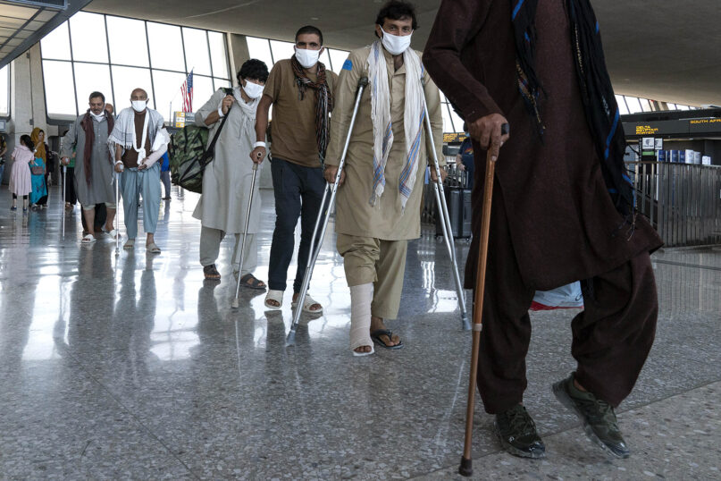Injured refugees evacuated from Kabul, Afghanistan, walk through the terminal before boarding a bus after they arrived at Washington Dulles International Airport, in Chantilly, Virginia, on Aug. 25, 2021. (AP Photo/Jose Luis Magana)