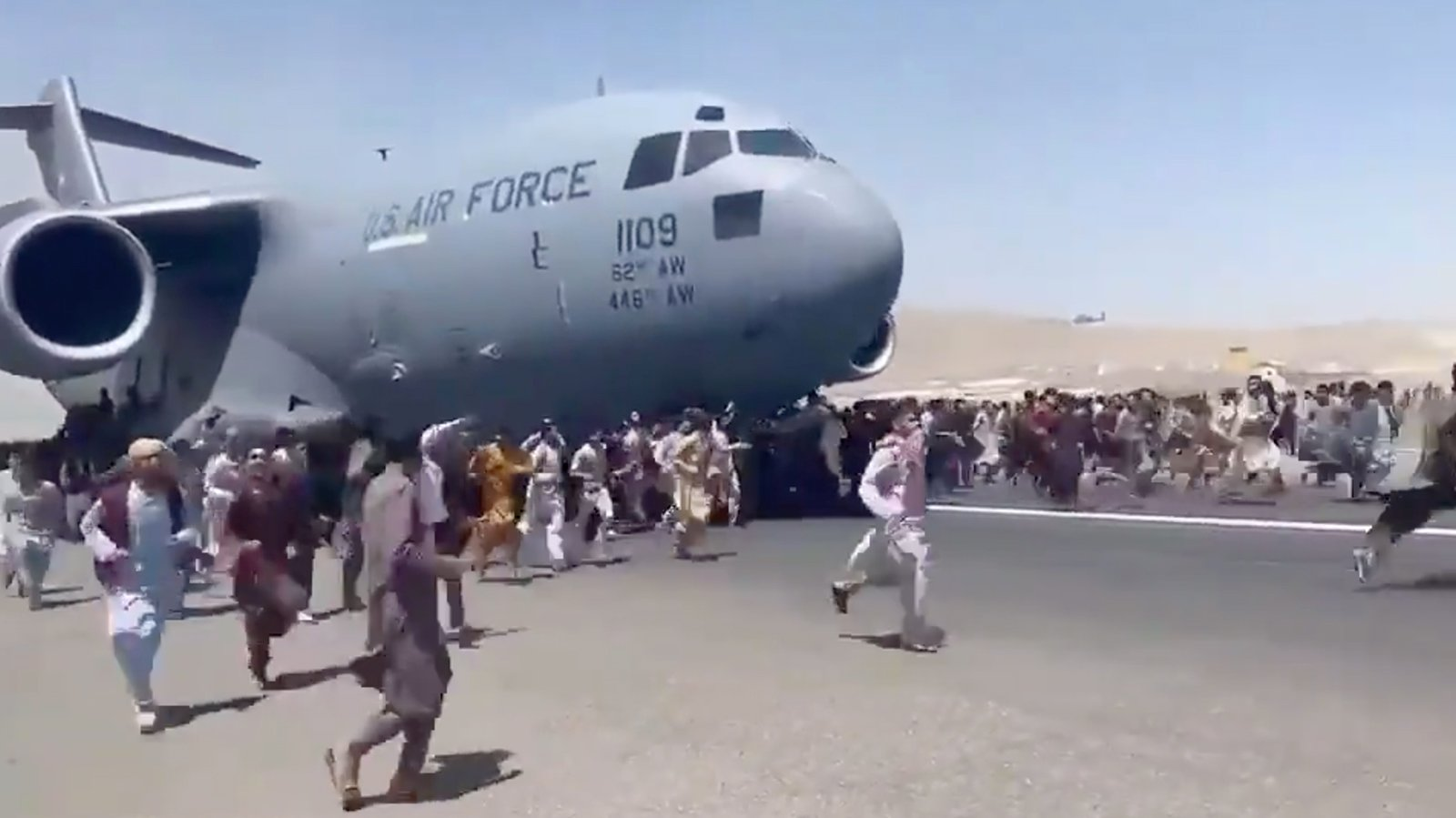 Hundreds of people run alongside a U.S. Air Force C-17 transport plane as it moves down a runway of the international airport, in Kabul, Afghanistan, Aug. 16, 2021. Thousands of Afghans rushed onto the tarmac at the airport, attempting to flee the Taliban. Video screengrab via Twitter/@Mukhtarwafayee