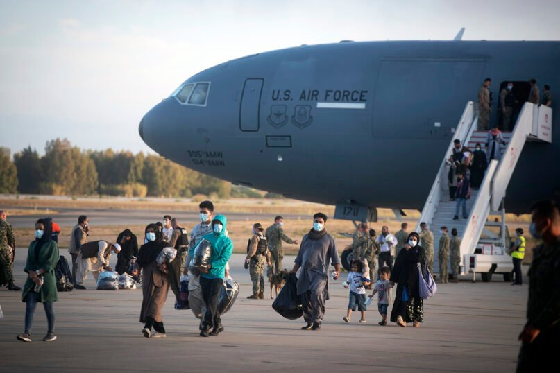 Evacuees from Afghanistan disembark from a U.S. Air Force plane at the naval station in Rota, southern Spain, on Aug. 31, 2021. The United States completed its withdrawal from Afghanistan late Monday, ending America's longest war.(AP Photo/ Marcos Moreno)