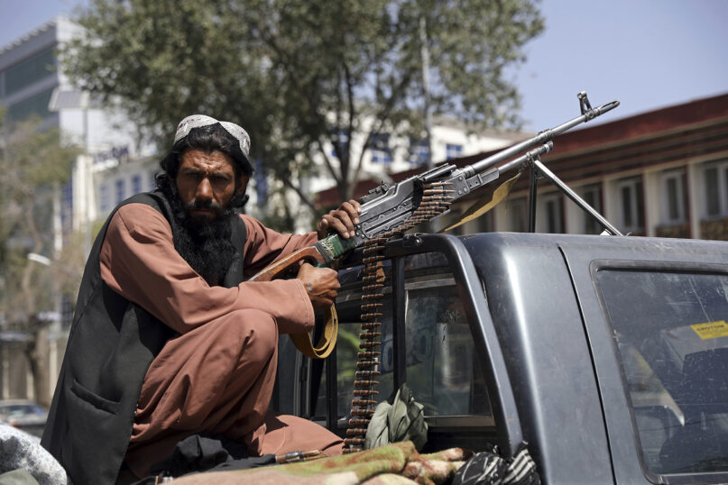 A Taliban fighter sits on the back of a vehicle with a machine gun in front of the main gate leading to the Afghan presidential palace, in Kabul, Afghanistan, Aug. 16, 2021. (AP Photo/Rahmat Gul)