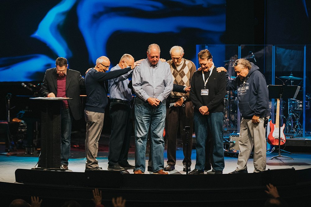People pray over new elders Brett Scott, center, and John Tunstall, center right, as they are affirmed and installed at Beach Church in Jan. 2021. Courtesy photo