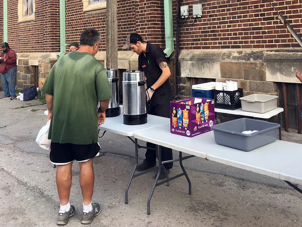 Manna Meal soup kitchen volunteers distribute food and drinks at St. Peter's Episcopal Church, Friday morning, July 30, 2021, in Detroit. RNS photo by Renée Roden