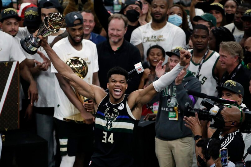 Milwaukee Bucks forward Giannis Antetokounmpo (34) celebrates with the MVP trophy, as teammates hold the championship trophy, after defeating the Phoenix Suns in Game 6 of basketball's NBA Finals, July 20, 2021, in Milwaukee. The Bucks won 105-98. (AP Photo/Aaron Gash)