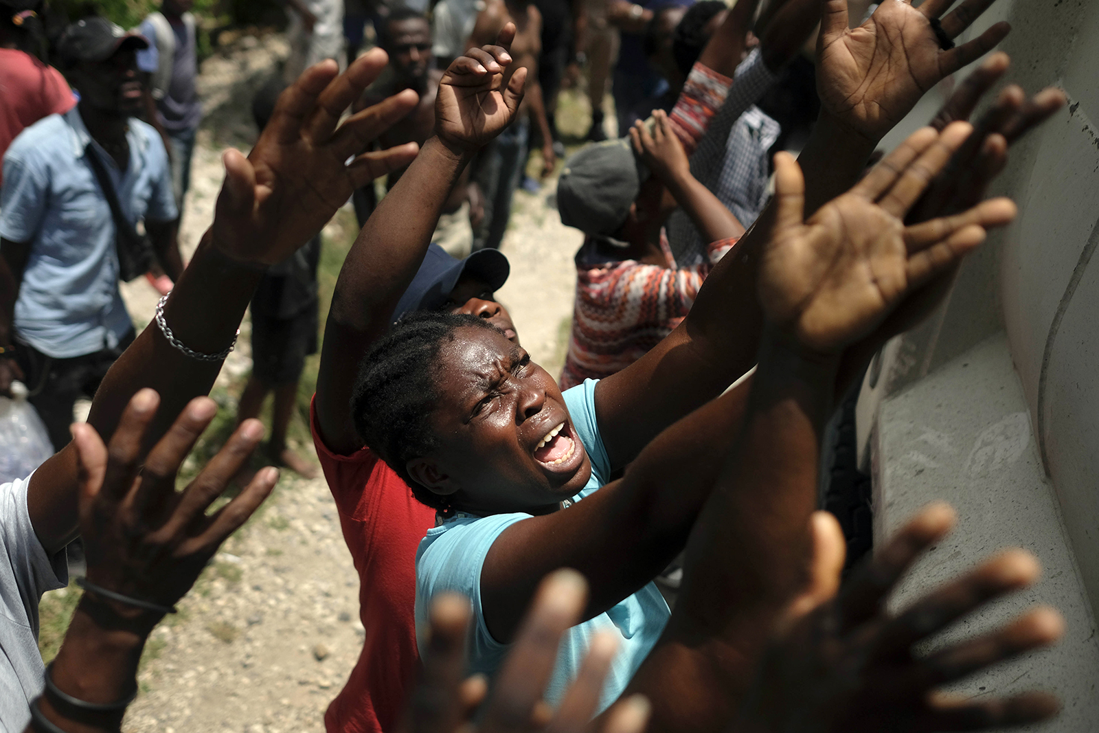 Earthquake victims reach for water being handed out with food distribution in the Picot neighborhood in Les Cayes, Haiti, Aug. 22, 2021, eight days after a 7.2 magnitude earthquake hit the area. (AP Photo/Matias Delacroix)
