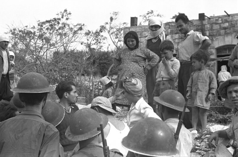 Villagers, top, and Israeli Defense Forces soldiers in Iqrit, northern Israel, on Nov. 3, 1948. The village was evacuated on Nov. 5, 1948. Photo via the Israeli Government Press Office/Creative Commons