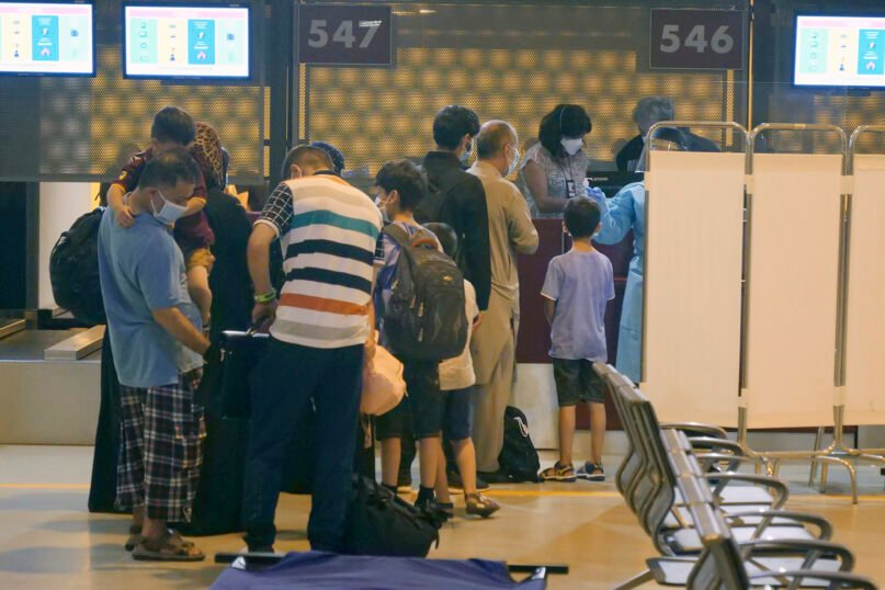Evacuees from Afghanistan queue in line after arriving at Rome's Leonardo da Vinci international airport in Fiumicino, early Tuesday, Aug. 24, 2021. (AP Photo/Paolo Santalucia)