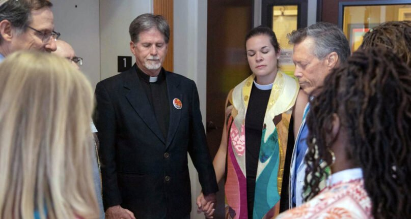 Clergy members hold hands during the blessing of a Whole Woman's Health clinic in Austin, Texas. Participants included the Rev. Jim Rigby of St. Andrew's Presbyterian Church in Austin, from center left in black;  the Rev. Katey Zeh, CEO of the Religious Coalition for Reproductive Choice; and the Rev. Mark Skrabacz, retired from San Gabriel UU Fellowship - Georgetown. Photo courtesy of Just Texas