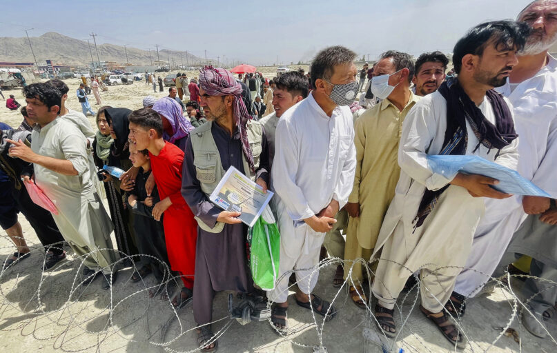 A man holds a certificate acknowledging his work for Americans, center, as hundreds of people gather outside the international airport in Kabul, Afghanistan, Aug. 17, 2021. (AP Photo)