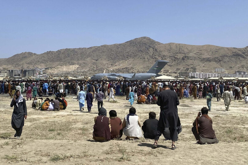 In this Aug. 16, 2021, file photo, hundreds of people gather near a U.S. Air Force C-17 transport plane along the perimeter at the international airport in Kabul, Afghanistan. After the Taliban takeover, employees of the collapsed government, civil society activists and women are among the at-risk Afghans who have gone into hiding or are staying off the streets. They hope for a way to leave their homeland. (AP Photo/Shekib Rahmani, File)