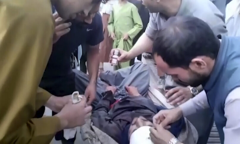 In this frame grab from video, people attend to a wounded man near the site of a deadly explosion outside the airport in Kabul, Afghanistan, Thursday, Aug. 26, 2021. Two suicide bombers and gunmen have targeted crowds massing near the Kabul airport, in the waning days of a massive airlift that has drawn thousands of people seeking to flee the Taliban takeover of Afghanistan. (AP Photo)