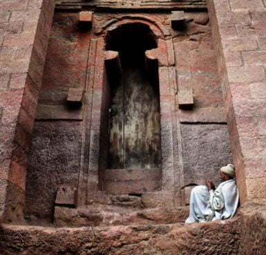 A man sits outside one of the rock churches in Lalibela, Ethiopia. Photo by Rod Waddington/Creative Commons