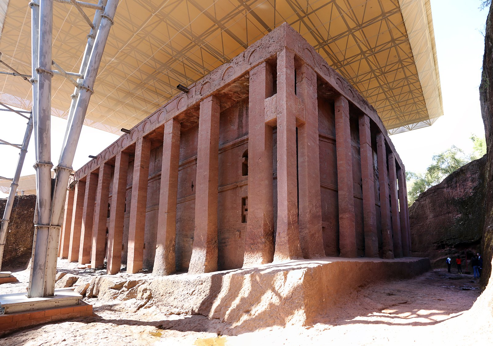 People stand beside the walls of Biete Medhane Alem, believed to be the largest monolithic church in the world, in Lalibela, Ethiopia. Photo by Sailko/Creative Commons