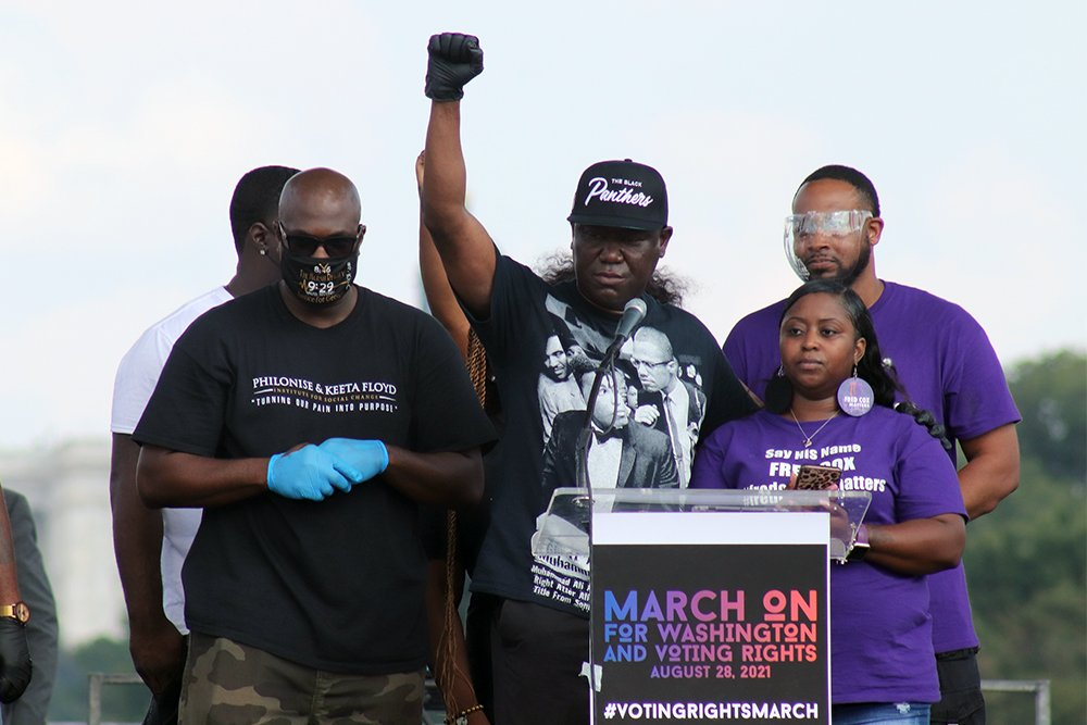Attorney Ben Crump stands with family members of people who have been killed in police violence, including Tenicka Shannon, right, mother of Fred Cox, during the March On for Voting Rights rally in Washington D.C., August 28, 2021. RNS photo by Adelle M. Banks