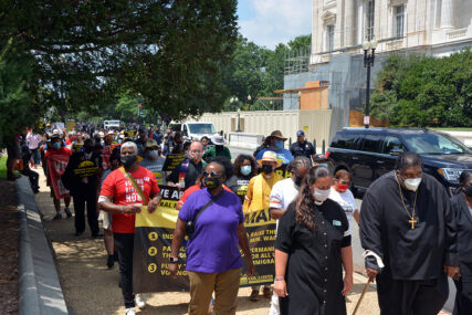 The Rev. William Barber, right, and the Rev. Liz Theoharis, second from right, lead a Poor People's Campaign demonstration march in Washington, Monday, Aug. 2, 2021. RNS photo by Jack Jenkins