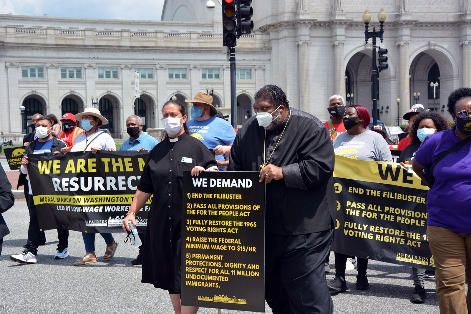 The Rev. Rev. Liz Theoharis, center left, and the Rev. William Barber lead a Poor People's Campaign demonstration march in Washington, Monday, Aug. 2, 2021. RNS photo by Jack Jenkins