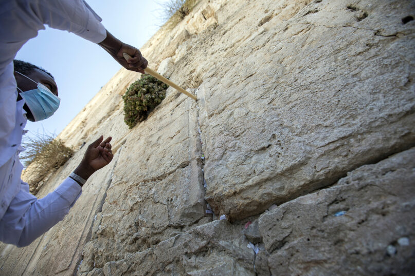 A worker removes prayer notes Aug. 25, 2021, left by visitors in gaps between stones at the Western Wall, the holiest site where Jews can pray in Jerusalem's Old City, ahead of Rosh Hashana, the Jewish new year. The notes are buried in a nearby cemetery in accordance with Jewish tradition. (AP Photo/Ariel Schalit)