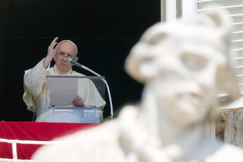 Pope Francis delivers his blessing as he recites the Angelus noon prayer from the window of his studio overlooking St. Peter's Square, at the Vatican, Sunday, Aug. 15, 2021. (AP Photo/Andrew Medichini)