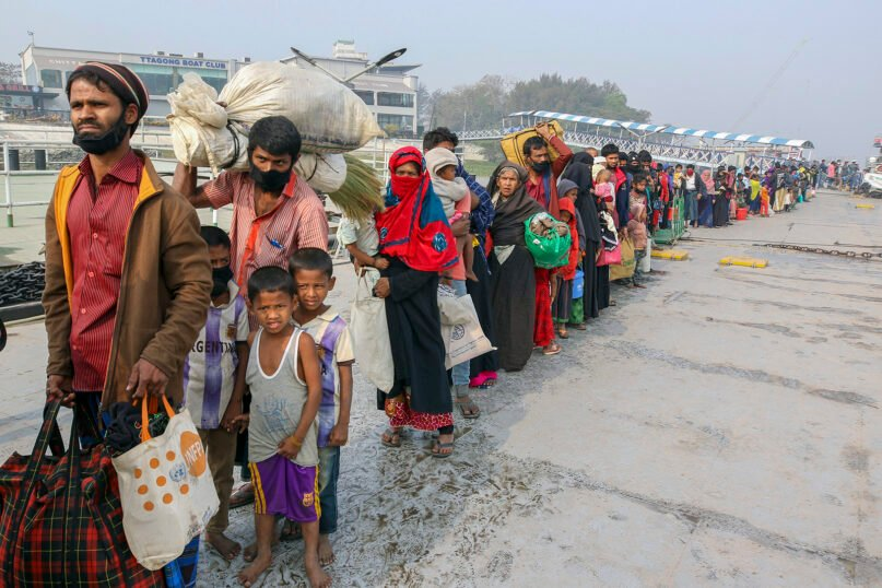 In this Feb. 15, 2021, file photo, Rohingya refugees headed to the Bhasan Char island prepare to board navy vessels from the southeastern port city of Chattogram, Bangladesh. Authorities in Bangladesh on Aug. 10, 2021, started vaccinating Rohingya refugees against coronavirus for the first time across massive camps where more than 1 million refugees from neighboring Myanmar have been sheltered, officials and the U.N. refugee agency said.  (AP Photo, File)