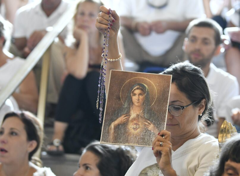 A woman holds a rosary and a picture of the Virgin Mary during a 2019 hearing  in Albany, N.Y., challenging the constitutionality of the state's repeal of the religious exemption to vaccination. (AP Photo/Hans Pennink)
