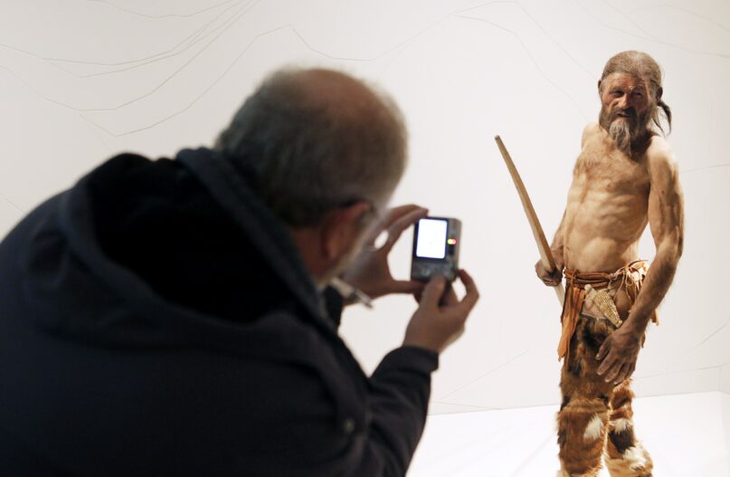 A man takes a picture of a statue representing the 5,300-year-old mummy named Ötzi, discovered in the  Italian Alps 30 years ago. (Andrea Solero/AFP via Getty Images)