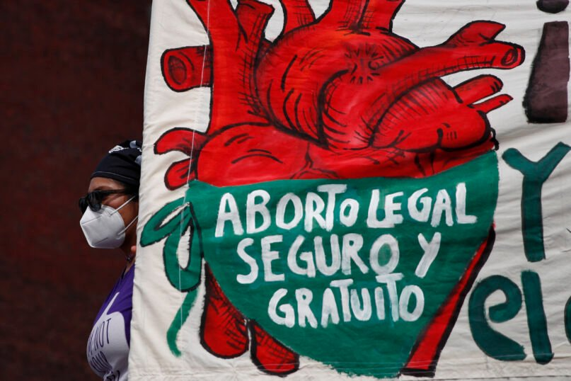 In this Sept. 28, 2020, file photo, a woman holds a banner reading, in Spanish,