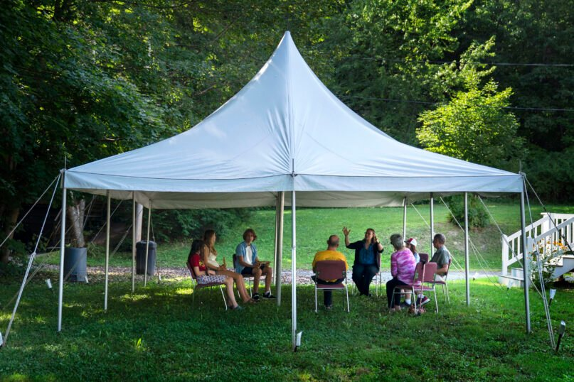 """A class in Judaism is held under a tent outside Temple Beth El, Aug. 30, 2021, in Augusta, Maine. The recent COVID-19 upsurge is disrupting plans for full-fledged in-person services. """"The ability to see people face to face is wonderful, whatever way they choose to come,"""" Rabbi Erica Asch says. """"But there's a little bit of sadness that we can't all be together the way we'd like."""" (AP Photo/Robert F. Bukaty)"""