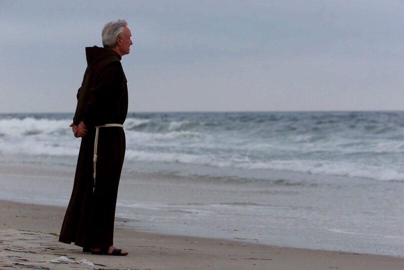 FILE - In this July 17, 2000 file photo, Father Mychal Judge, a chaplain with the New York City Fire Department, stands at the shore before a service where 230 candles were lit for the July 17, 1996 victims of TWA Flight 800, at Smith Point Park in Shirley, N.Y. Judge left a uniquely complex legacy that continues to evolve 20 years after his death. (AP Photo/Ed Betz, File)