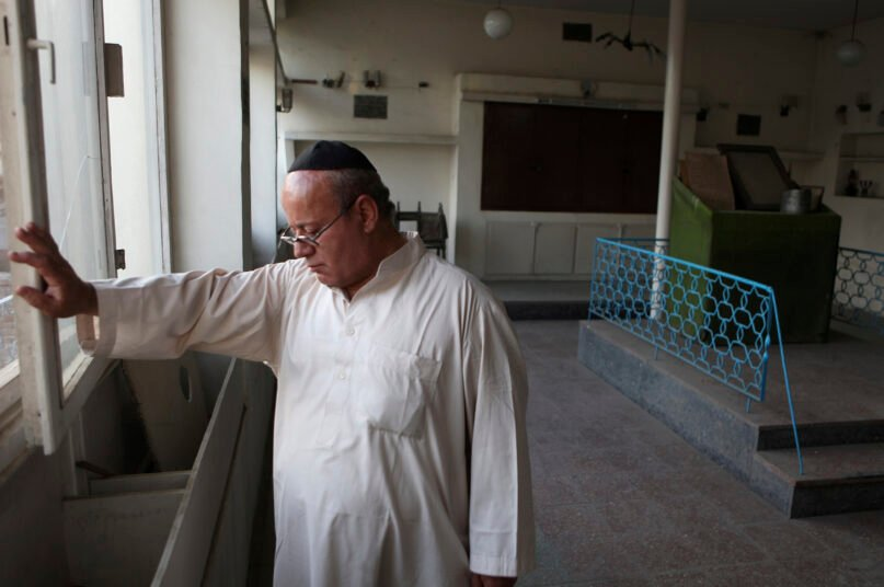 FILE - In this Aug. 29, 2009 file photo, Zebulon Simentov, the last known Jew living in Afghanistan, closes the window to the synagogue he cares for in his Kabul home. Simentov who prayed in Hebrew, endured decades of war as the country's centuries-old Jewish community rapidly dwindled has left the country. The Taliban takeover in August, 2021, seems to have been the last straw. (AP Photo/David Goldman, File)