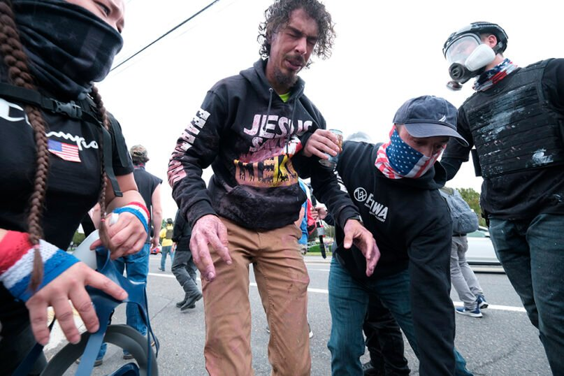 A street preacher attending a Proud Boys rally receives help after getting pepper sprayed by anti-fascist protesters during clashes between the opposing groups on Sunday, Aug. 22, 2021, in Portland, Ore. (AP Photo/Alex Milan Tracy)