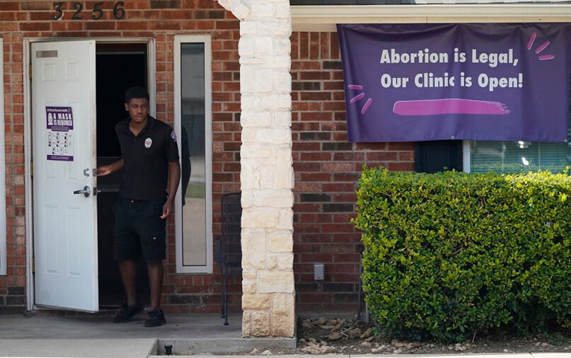 In this Sept. 1, 2021, file photo, a security guard opens the door to the Whole Women's Health Clinic in Fort Worth, Texas. Even before a strict abortion ban took effect in Texas Sept. 1, clinics in neighboring states were fielding more and more calls from women desperate for options. The Texas law, allowed to stand in a decision Sept. 2, 2021, by the U.S. Supreme Court, bans abortions after a fetal heartbeat can be detected, typically around six weeks. (AP Photo/LM Otero)