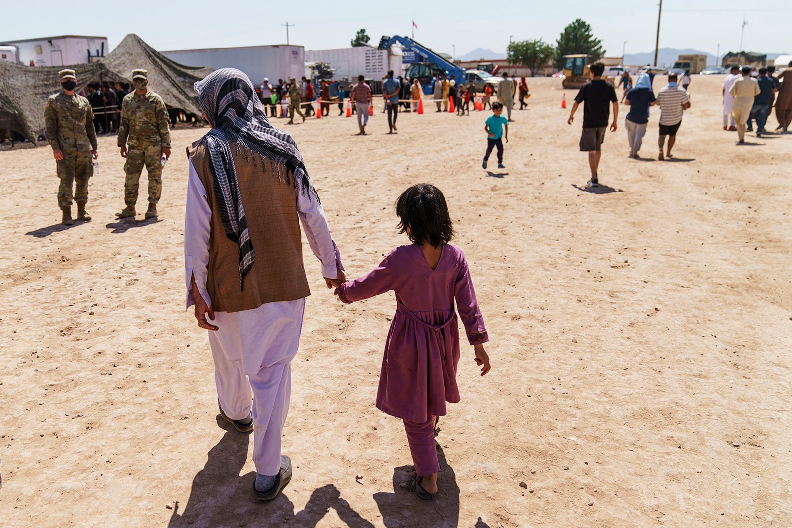 A man walks with a child through the Doña Ana Village of Fort Bliss, where Afghan refugees are being housed, in New Mexico, Sept. 10, 2021. The Biden administration provided the first public look inside the U.S. military base where Afghans airlifted out of Afghanistan are screened, amid questions about how the government is caring for the refugees and vetting them. (AP Photo/David Goldman)