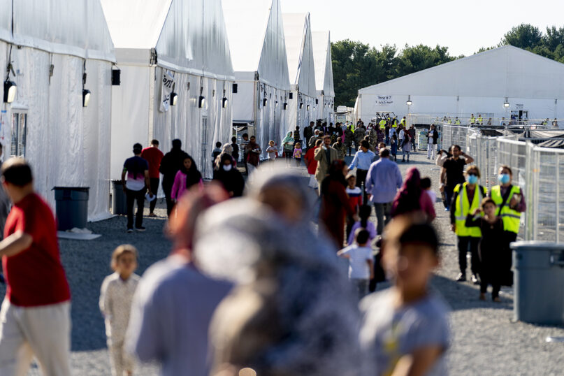 Afghan refugees walk through a refugee camp on Joint Base McGuire Dix Lakehurst, N.J., Monday, Sept. 27, 2021. The camp currently holds approximately 9,400 Afghan refugees and has a capacity to hold up to 13,000. (AP Photo/Andrew Harnik)